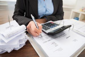 Close-up Of Businessperson Calculating Bills At Desk